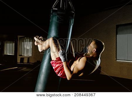 The Boxer In The Gym Hung On A Boxing Bag And Makes Twists For The Abdominal Muscles.