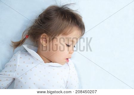 little girl portrait looking down with interest lying on white blanket