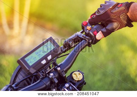 Man hand clicking on control button rear stop signal of electric bicycle. Ebike bicycle environmentally friendly eco e-mountainbike transport. Healthy lifestyle