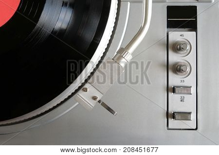 Vintage turntable in silver case with buttons and knobs on control panel with vinyl record with red label studio shot top view