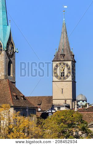 Well-known architectural landmarks of the city of Zurich in Switzerland: clock tower of the Saint Peter Church, partial view of the clock tower of the Fraumunster cathedral. The picture was taken in the beginning of October.