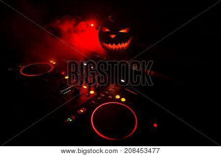 Halloween Pumpkin On A Dj Table With Headphones On Dark Background With Copy Space. Happy Halloween