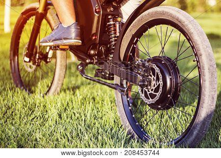 Man biker sitting on electric bike. Ebike bicycle environmentally friendly eco e-mountainbike transport. Healthy lifestyle