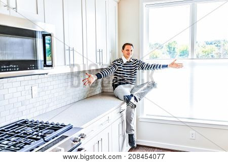 Young man sitting on kitchen countertop with outstretched open arms in clean modern white home design