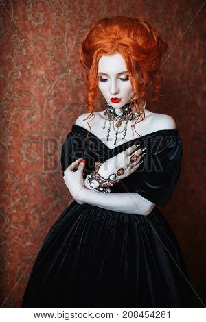 Vampire clothes for Halloween. Girl dress gothic outfit for halloween. Interesting gothic look for Halloween. Celebrate Halloween. Prepare an interesting look on Halloween. Halloween woman is a vampire with red hair in a black dress