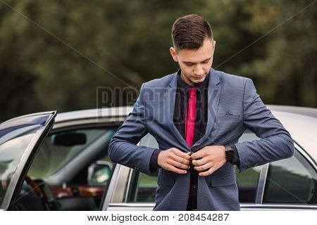 Successful rich businessman in a dark rich business suit with a red tie against the background of a car. Stylish rich man. Fashionable watch on hand. Rich business man button up a button on jacket