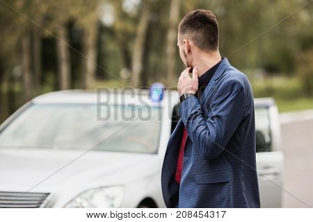 Successful businessman in a dark business suit with a red tie. The security looks at the car. Hijacking machines. Security guard. Security near the car. Confident security guard in a business suit