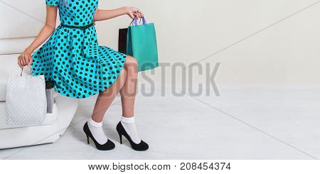 Girl in blue dress and black shoes with shopping bags on a white background. Black Friday shopping. A girl loves shopping. Shopping concept on a white background. Stylish model with shopping bags. Do shopping on a black Friday