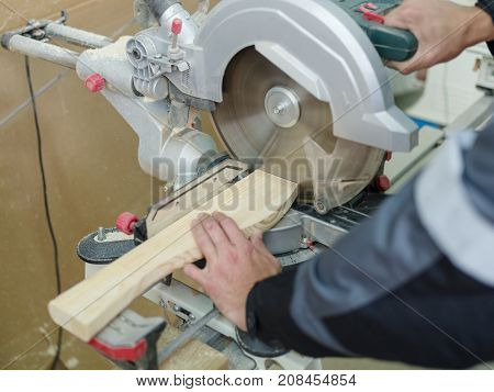 Gray machine circular saw, the worker saws a piece for further work