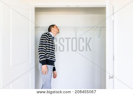 Young Man Checking Looking Inside Small Closet In New Room After Or Before Moving In, During Open Ho