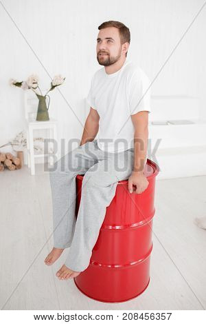 Young attractive man in home clothes sitting on a red barrel in the middle of the room looking to the side and posing on a camera isolated on a white background. Full lenght of man.