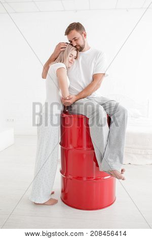 Young loving couple hugging each other, smiling and posing on camera isolated on a white background. Full lenght of beautiful couple.