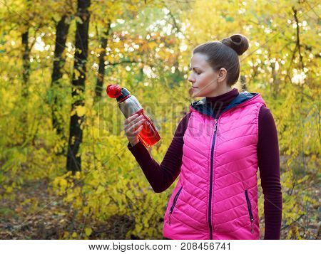 Beautiful fitness sport girl in sportswear with sports water bottle or isotonic drink in hand in autumn forest