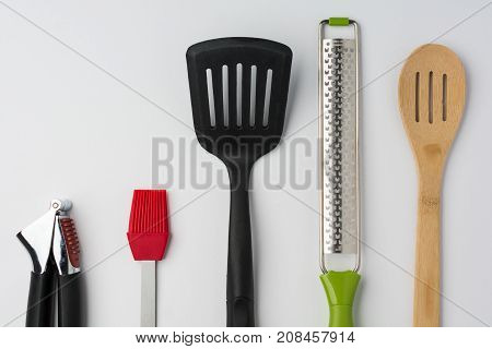 Garlic Press Brush Spoon Spatula Zester on White Background Cropped Close