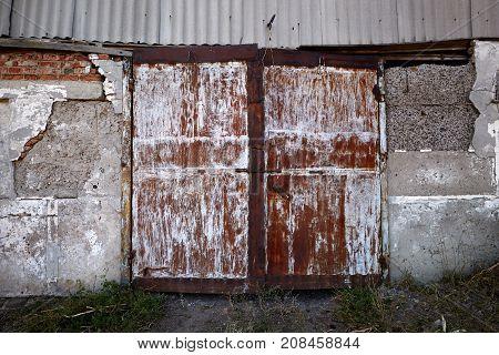 Old metal weathered door of abandoned barn