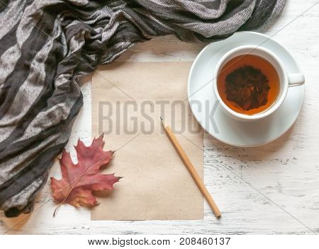 A Cup Of Tea On A Table With A Striped Warm Scarf Or Stole And A Sheet Of Paper For Notes Or Sketche