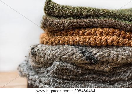 Stack of Handmade Warm Knitted Socks Scarfs Mittens From Rough Wool Yarn Brown Beige Grey on Wood Table. Close up. Winter Autumn Eco Fashion Kinfolk Style. Natural Materials