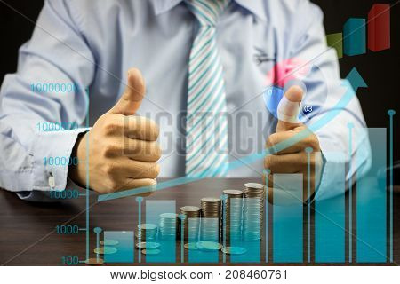 businessman show thumb with stacked of coins with graph mixed media