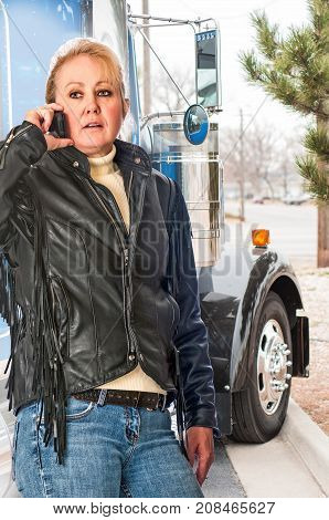 Woman truck driver getting a load delivery time update from her dispatcher on the cell phone.