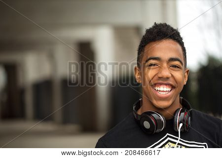 Happy young teenager listening to music outside.