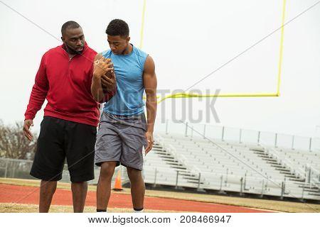 Coach training a high school athlete for football.