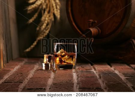 Glass Of Whiskey And Wooden Barrel In Cozy Cellar