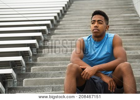 Young African Amerian teenage athlete in deep thought.