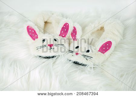 pair of cute bunny slippers on white fur rug