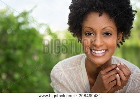 Happy confident African American woman smiling outside.