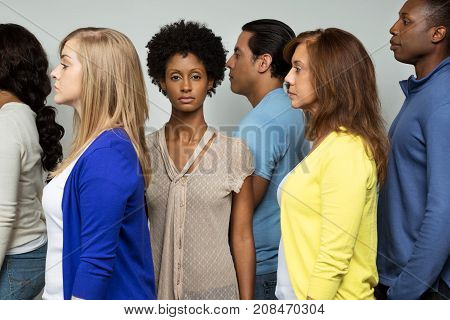 Lonely woman standing in a crowd of diverse people.