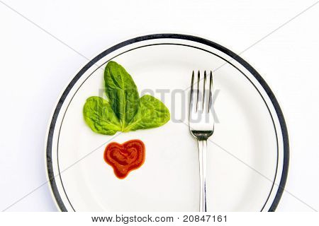 Spinach leaves with and a fork on a plate