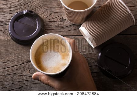 Lot of empty cups of coffee and a full cup of coffee in the hands of a man. Excessive coffee consumption is dangerous to health