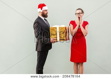 Bearded Man In Christmas Hat Give A Present Beautiful Woman In Red Dress With Shocked Face.