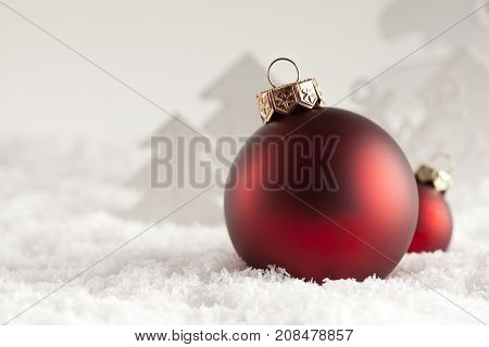 Christmas baubles and xmas trees on snow