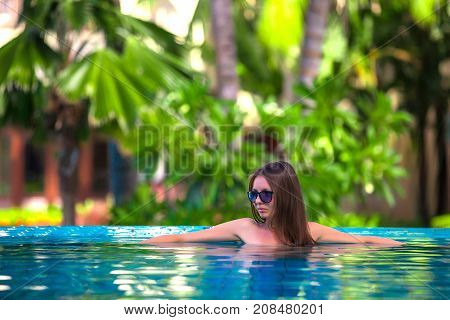 A girl in the pool in sunglasses grins and looks away. Woman posing in the pool, Sanya, Hainan, China.