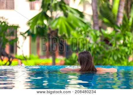 A girl turned back leaned against the edge of the pool in sunglasses. Woman posing in the pool, Sanya, Hainan, China.