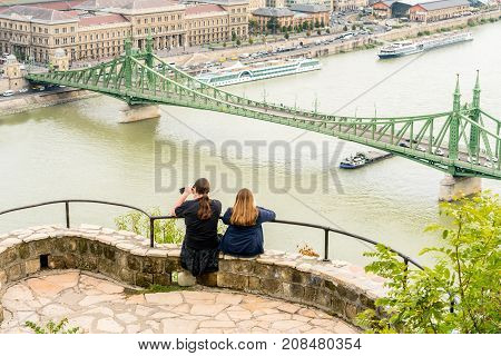 A young couple sitting at a viewpoint up high taking pictures of Liberty bridge over the Danube river Budapest Hungary.