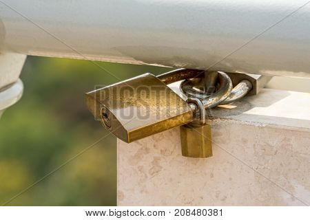 Close up of three padlocks attached to a steel railing on white marble and green background.
