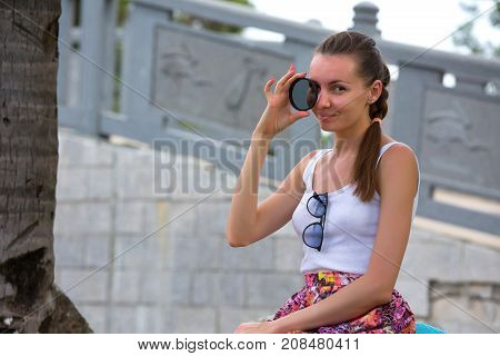 A girl posing with a light filter lens in the park. A woman in Sanya, Hainan, China.