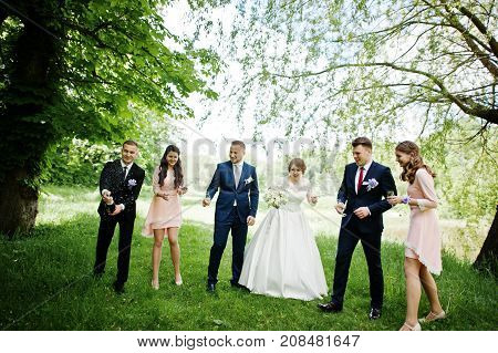 Wedding Couple, Bridesmaids And Groomsman Waiting For Best Man To Open Up A Bottle Of Champagne In A
