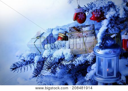 Natural fir tree covered with snow.. Christmas decoration hanging on fir tree branch. Gift box laying on branch .
