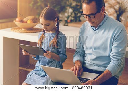 Contemporary parenting. Side view on a focused girl and her father working with computers and ignoring the presence of each other while both sitting in the kitchen and spending time together.