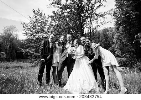 Crazy And Happy Newlyweds Having Fun With Bridesmaids And Groomsmen In The Park.