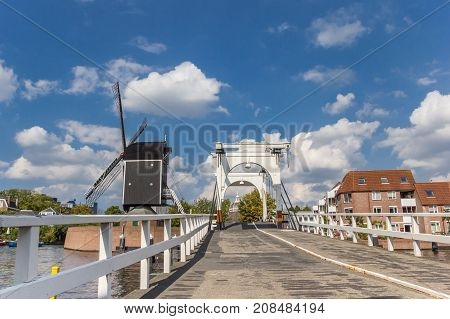 White Bridge And Historic Windmill At A Canal In Leiden