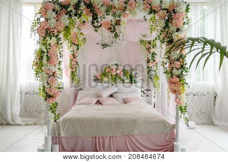 Honeymoon Suite With Canopy Bed, Free Space. Luxurious Wood Canopy Bed With Flowers And Pillows On I
