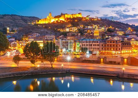 Amazing view of Olt town with Narikala ancient fortress, St Nicholas Church and Kura river in night Illumination during evening blue hour, Tbilisi, Georgia.