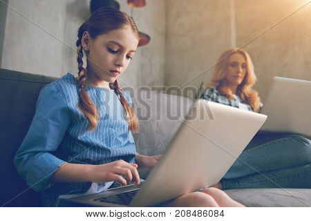 Innovative upbringing. Selective focus on a little girl totally absorbed in the process of using her laptop sitting next to her busy working mother at home.