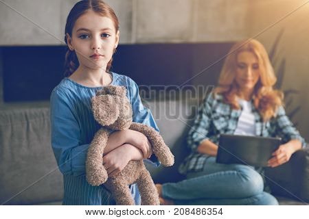 Lack of love. Waist up shot of an unhappy child hugging her bunny toy looking into the camera with eyes full of sadness while her ignoring mother working on laptop in the background.