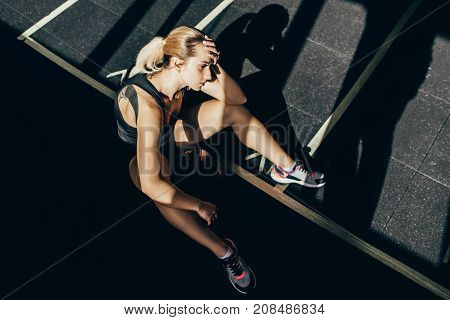 Exhausted Sportswoman Sitting On Floor