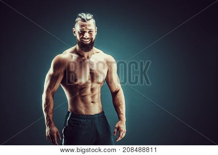 Smiling guy bodybuilder posing. Beautiful sporty guy male power. Fitness muscled man in studio. Dark background.